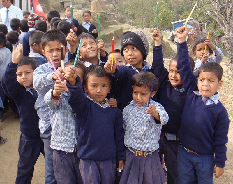 Nepalesische Schuldinder halten Bunte Stifte in die Luft