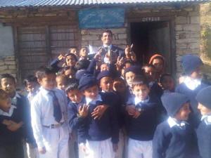 Die Schulkinder und Direktor Shamser Thapa stehen mit einem Päckchen aus Deutschland vor der Diamond Hill Academy